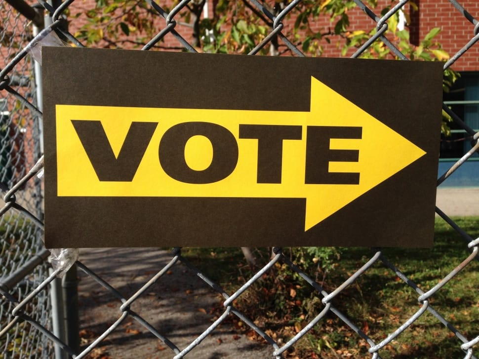 "Simple sign reading ""VOTE"" with a yellow arrow attached to a chainlink fence"