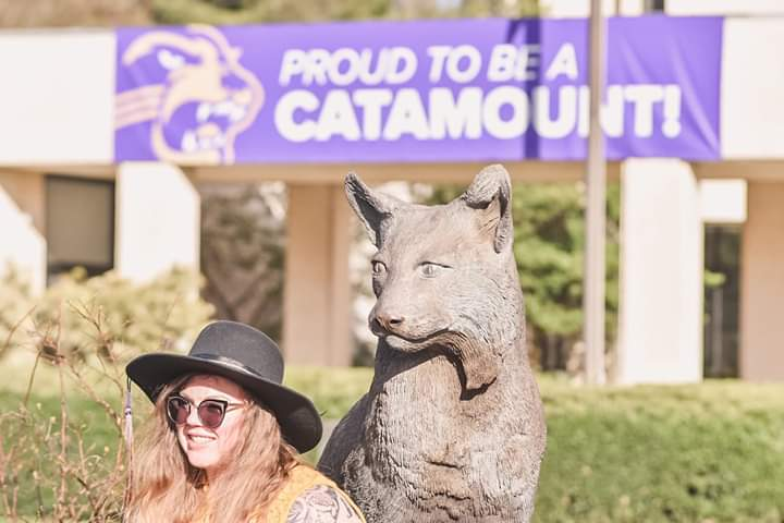 "Picture of the author in front of a sign reading ""Proud to be a catamount!"""