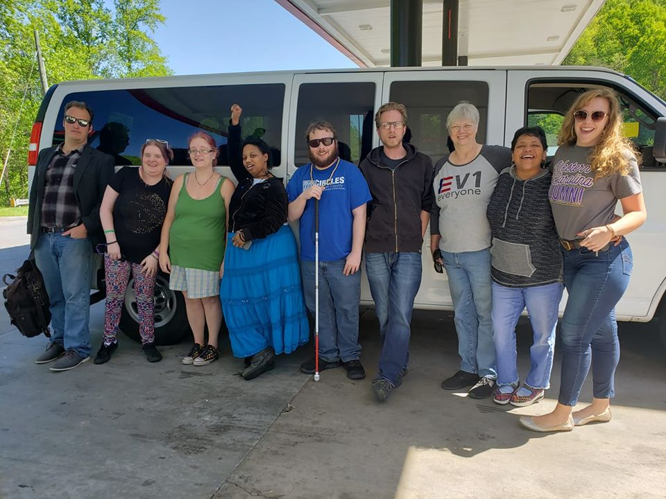 Down Home members gather outside a white van getting ready for a road trip. Quinterra Jones stands with fist raised above her head, wearing a blue skirt.