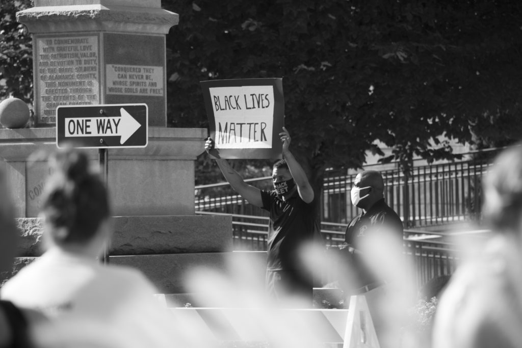 Man standing next to a monument holding Black Lives Matter sign above his head.