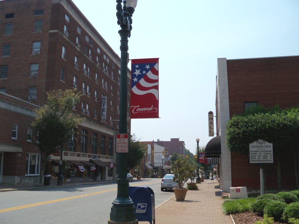 Photo of downtown Concord North Carolina with brick buildings and a commercial main street.